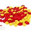 Red and yellow medicinal pills on a white background with space  — Stock Photo