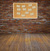 Cork bulletin board with old paper note on brick wall. — Stock Photo