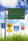 Traffic signs on green grass and blue sky. — Stock Photo