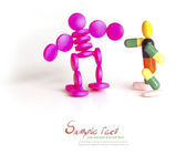 Two colorful robot (made of capsules and tablets) stand on white — Photo