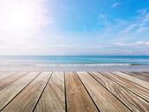Terraza de madera en la luz de sol y playa — Foto de Stock