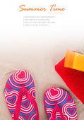 Flipflops ,sunscreen,towel on sand beach — Stock Photo