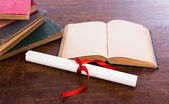 Diploma with old book isolated on a white background. — Stock Photo