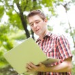 Portrait of young man with laptop outdoor — Stock Photo