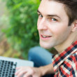 Portrait of young man with laptop outdoor — Stock Photo #30516655