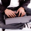Stock Photo: Portrait of young business man sitting using a laptop