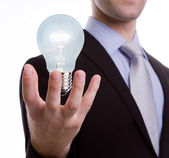 Business man holding light bulb — Stock Photo