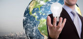 Business man holding light bulb (Elements of this image furnish — ストック写真