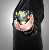 Business man holding the small world in his hands against white — Stockfoto