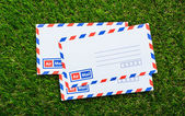 Letters air mail on green grass — Stock Photo