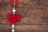 Red heart hanging on old wood background. — Stock Photo