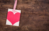 Red paper heart hanging on old wood background. — Stock Photo