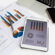 Financial charts on table with tablet phone and pen — Stock Photo #41232659