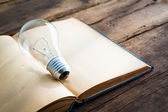 Vintage book and light bulb on wood table — Stock Photo