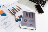 Financiële grafieken op de tabel met telefoon van de tablet pc- en peninstellingen — Stockfoto