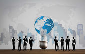 Business people silhouettes with bulb and world map — Stock Photo