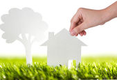 Paper cut of family house and tree on fresh spring green grass — Stock Photo