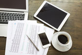 Laptop, tablet , smartphone and coffee cup with  financial docum — Stock Photo