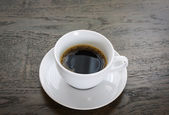 Coffee in white cup on wood table — Stock Photo