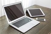 Laptop with tablet and smart phone on table — Stock Photo