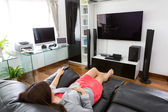 Business young woman watching TV in modern home office with comp — Stock Photo