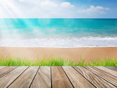 Wood terrace on the beach with green grass and sun light — Stock Photo