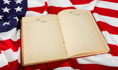 Vintage open book on American flag — Stock Photo