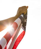 Hand hold American flag with sun light — Stock Photo