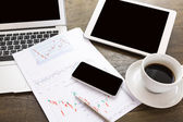 Ordinateur portable, tablette, smartphone et café tasse avec les documents financiers — Photo