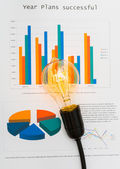 Light bulb with business graph — Stock Photo