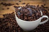 Coffee cup and coffee beans on a wooden table — Stock Photo