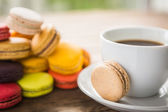 French colorful macarons with cup of coffee — Stock Photo