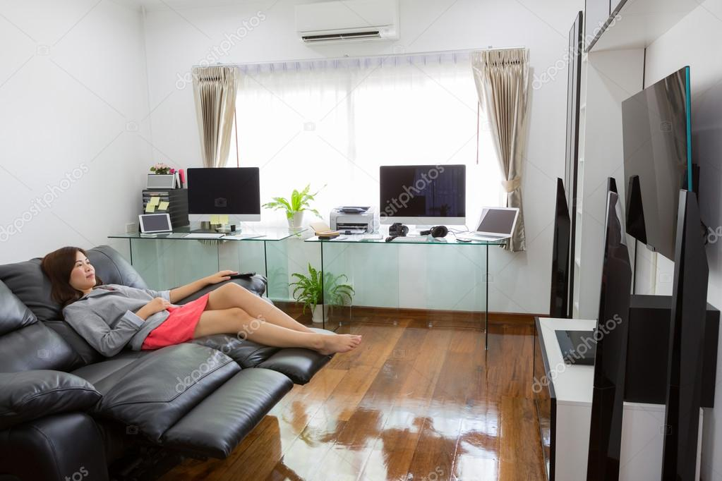 Joven mujer de negocios viendo la tv en la oficina moderna for Oficina moderna en casa