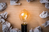 Light bulb with Crumpled paper on wood background — Stock Photo