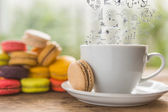 Coffee cup and French colorful macarons with business graph on s — Stock Photo