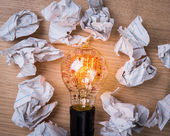 Light bulb  and  drawing graph inside with Crumpled paper on woo — Stock Photo