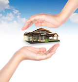 House in human hand over blue sky — Stock Photo
