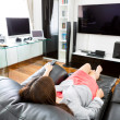 Business young woman watching TV in modern home office with comp — Photo #51779217