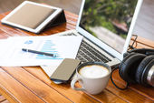 Laptop, tablet , smartphone and coffee cup with financial docume — Stock Photo