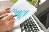 Close-up of business person use laptop with financial diagram — Stock Photo