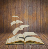 Open flying old books in wood room — Stock Photo