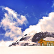 Wooden cottage and buried hut on peak of Snow Mountain — Stock Photo