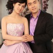 Loving Chinese young couple staind in balcony - Stock Photo