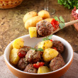 Meatballs with tomato sauce with potatoes in broth - Stock Photo