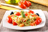 Spaghetti with fresh tomatoes, olives and mint — Stock Photo