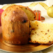 Table with panettone and christmas decorations on complex background - Stock Photo