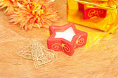 Chrysanthemum, gift and red candle on gold — Stock Photo