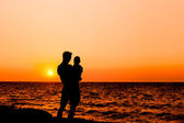 Father and son at sunset sea — Stock Photo