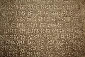 Escritura cuneiforme antigua sobre fondo de piedra — Foto de Stock