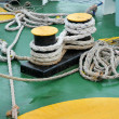 Old ropes around mooring bollard in a deck — Stock Photo